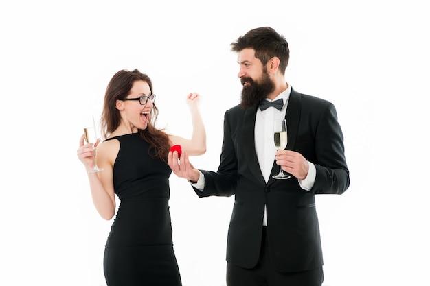 그녀는 그렇다고 말했다. 수염을 기른 남자와 여자는 기념일을 축하합니다. 사랑 데이트 기념일에 커플입니다. 커플 남자 턱시도와 샴페인 로맨틱 기념일을 가진 여자. 제안 또는 약혼 개념입니다.