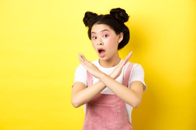 그녀는 아니오라고 말합니다. 아시아 아름다움 소녀 메이크업, 표시 크로스 기호, 중지 및 제안 거부, 노란색에 실망 서.