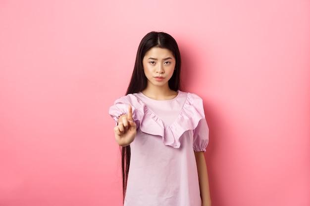 Она говорит нет. серьезная азиатская девушка трясет пальцем в стоп-жесте, запрещает и не соглашается с человеком, ругая плохое поведение, стоя на розовом фоне.