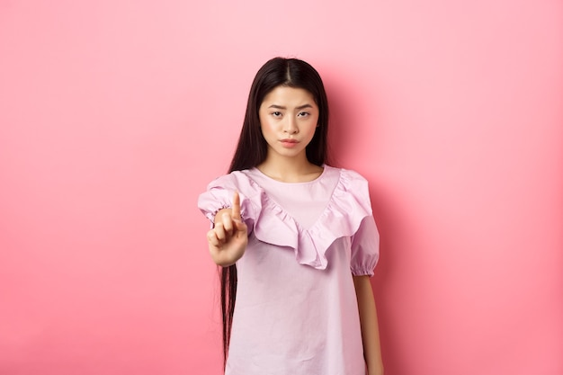She says no. serious asian girl shaking finger in stop gesture, prohibit and disagree with person, scolding bad behaviour, standing against pink background.