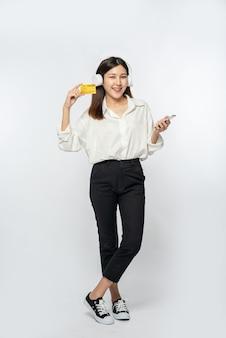 彼女は買い物に行き、クレジットカードとスマートフォンを持って行くために白いシャツと黒いズボンを着ていました