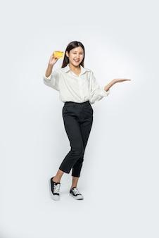 Она была одета в белую рубашку и темные брюки, чтобы ходить по магазинам и держать кредитную карту.
