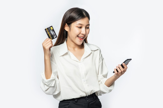 She was dressed in a white shirt and dark pants to go shopping and hold a credit card and smartphone