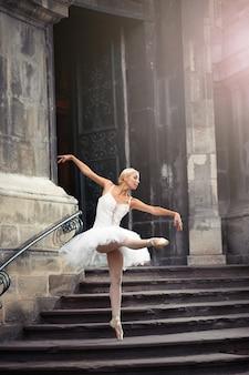 彼女はインスピレーションを探しに行きました。古い家の近くで優雅に踊るバレリーナの全身像