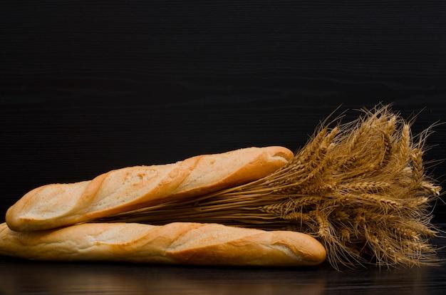 黒い背景に束と 2 つの白いパン、テキスト用のスペース