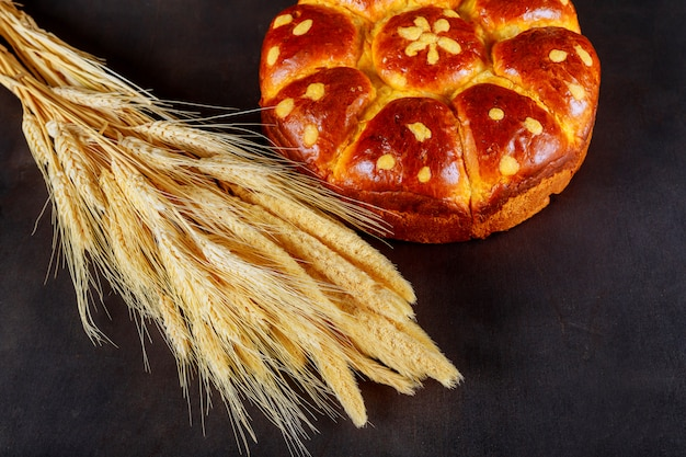 Sheaf of wheat and sweet pie on black