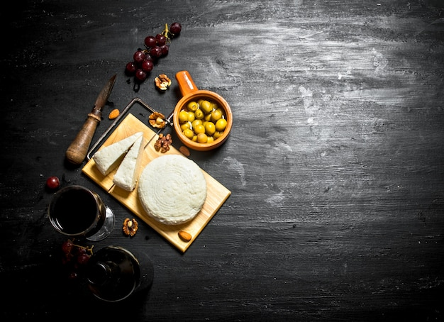 Sheep cheese with red wine , nuts and olives .