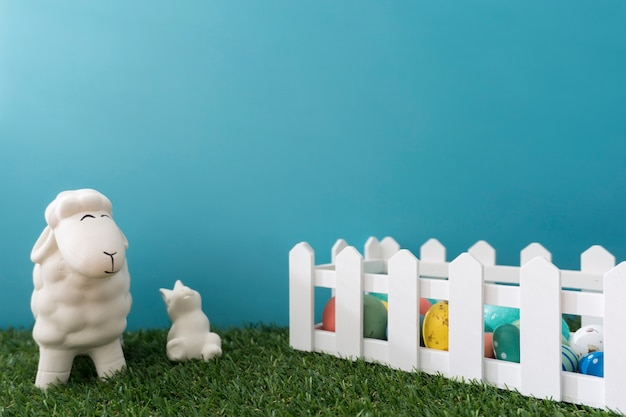 Sheep and rabbit close to a wooden fence with easter eggs