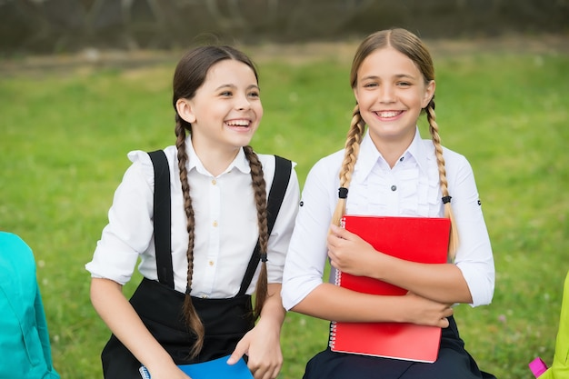 Sheer carelessness. happy childhood. back to school. teen pupils ready for lesson. prepare to exam. study together outdoor. small girls with backpacks. children hold notebook for making notes.