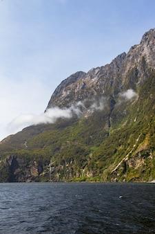 Отвесные скалы, поросшие зеленью на берегу фьорда.