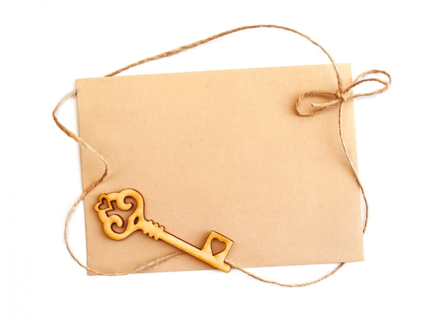 Sheet of kraft paper with key and rope to the frame and copyspace