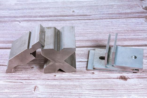 Инструмент и оборудование для гибки листового металла на деревянном фоне. специальная гибочная машина формовочная штамповка и штамп. инструмент для гибки пресса, инструмент для гибки, штамповочный пресс и штамп.
