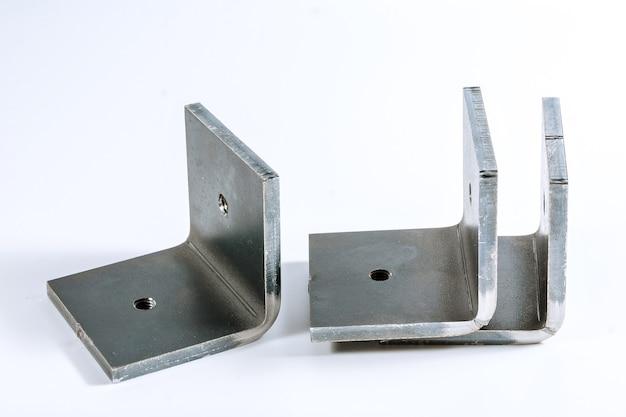 Изделие из листового металла после обработки на гибочном станке. инструмент и оборудование для гибки листового металла, изолированные на белом фоне. специальная гибочная машина формовочная штамповка и штамп.