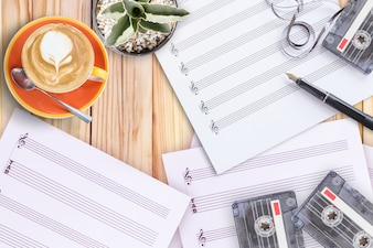 Sheet music cactus fountain pen tape cassette and coffee latte on wooden table