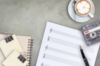 Sheet music fountain pen tape cassette and coffee latte on wooden table