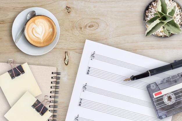 木製テーブル上の楽譜の万年筆のテープカセットとコーヒーラテ