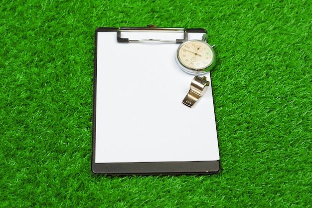 Лист бумаги и спортивного инвентаря на траве крупным планом