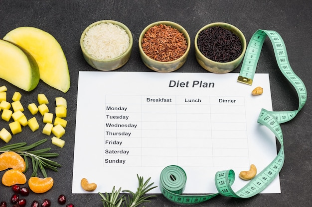 1週間のダイエット計画が記載された紙。ご飯とボウル。テーブルの上のマンゴーとマンダリンのスライス。巻き尺。フラットレイ