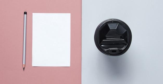 ペン、灰色のピンクの背景にコーヒーカップと紙のシート。ミニマルなコンセプト