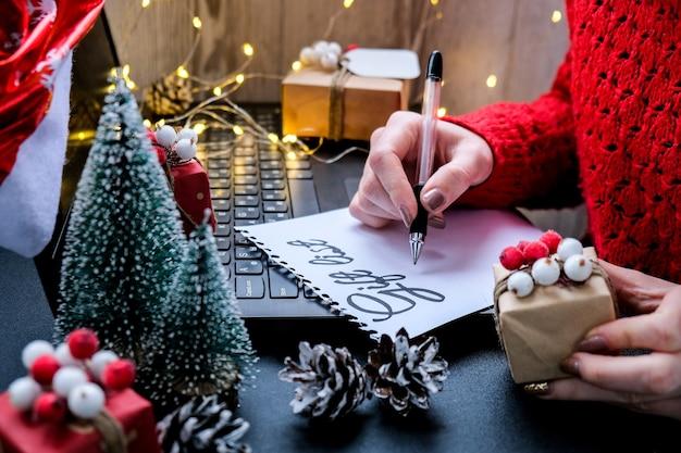 크리스마스 장식에 대한 텍스트 gift list가 있는 종이, 산타 모자를 쓴 노트북. 휴일 온라인 쇼핑. 겨울 세일. 크리스마스와 새해 준비