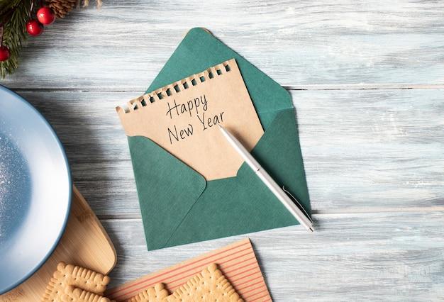 木製の背景に封筒に新年あけましておめでとうございますのテキストと紙のシート