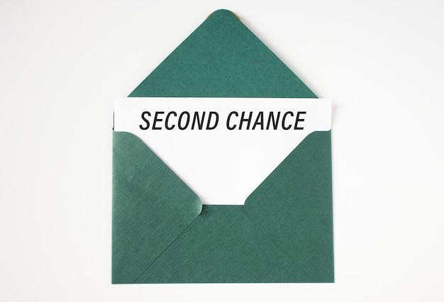Лист бумаги с текстом: «второй шанс», вложенный в зеленый конверт.