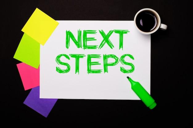 Next stepsという言葉が書かれた紙、一杯のコーヒー、メモ用のカラフルなステッカー、黒い表面に緑色のマーカー。