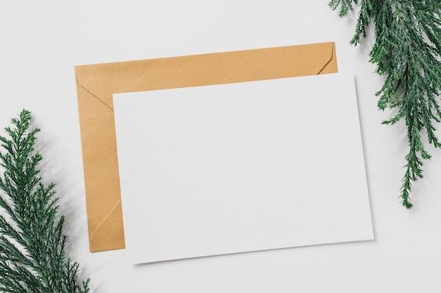 Лист бумаги с желтым конвертом на столе
