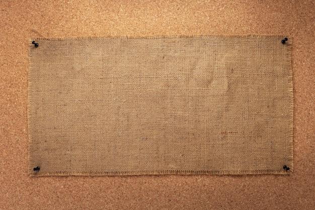 背景としてコルクボードに固定された袋ヘシアン黄麻布テクスチャのシート