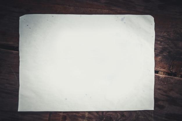 나무 표면에 흰 종이 한 장입니다. 나무 표면에 누워 흰 종이의 빈 조각. 추상 기본 기본 배경 배경 막입니다. 텍스트를 위한 공간