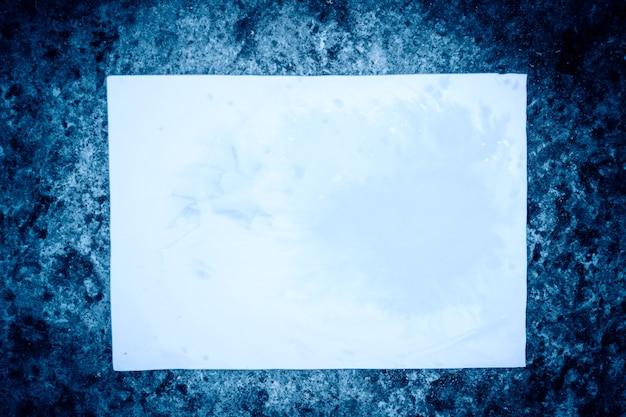 푸른 돌 표면에 흰 종이의 시트입니다. 푸른 돌 표면에 누워 흰 종이의 빈 조각. 추상 기본 기본 배경 배경 막입니다. 텍스트를 위한 공간