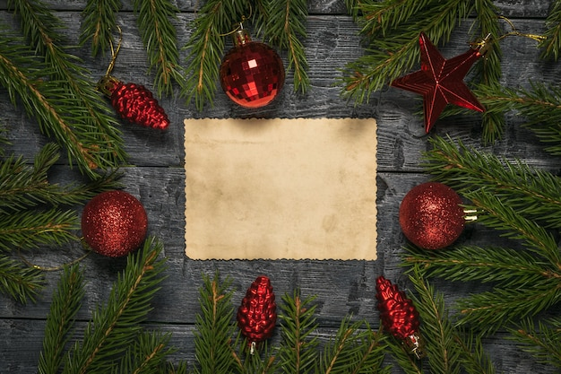 A sheet of old paper in the center of the table between the branches of a fir tree and glass toys