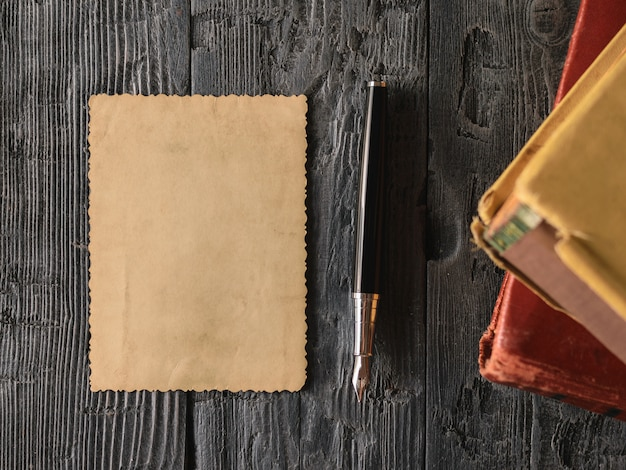 A sheet of old paper and a fountain pen with books on wood