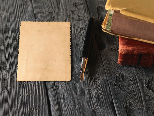 A sheet of old paper and a fountain pen with books on a wooden table. retro writing paper.