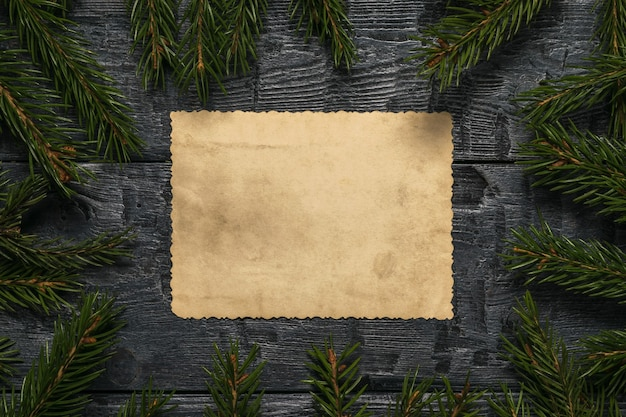 A sheet of old paper on a wooden table in thick spruce branches. a letter requesting a gift.