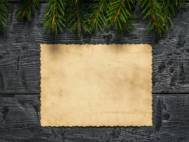 A sheet of old worn paper on a wooden background with fir branches. form for wishes and greetings. a letter requesting a gift.