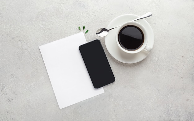 Sheet of paper, empty blank, notepad, pen, phone and cup of coffee espresso on concrete, gray background. planning concept, list, workspace. flat lay with copy space.