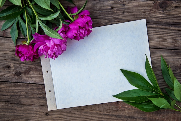 A sheet of paper and a few pink peonies on wooden background with copy space as a postcard
