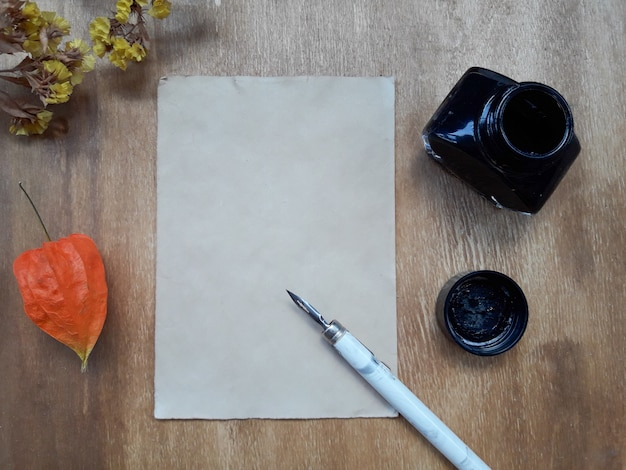 Sheet of paper, an inkwell and dry flowers