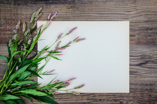 Sheet of paper and the little pink flowers on wooden background