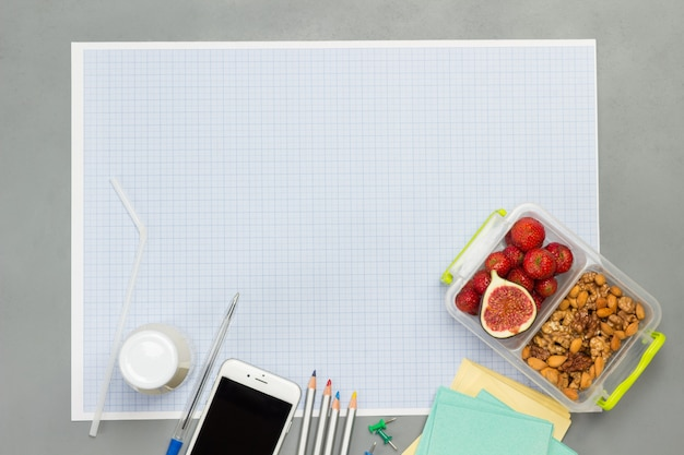 Sheet of paper in small blue cell with lunchbox with fruits and nuts. flat lay