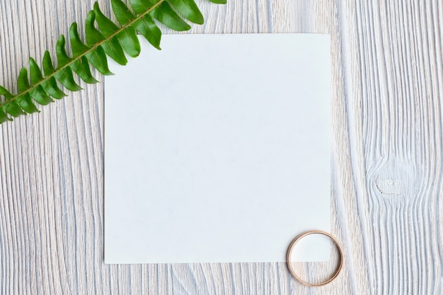 A sheet of paper with a green branch and a golden wedding ring. the concept of a love note. top view.