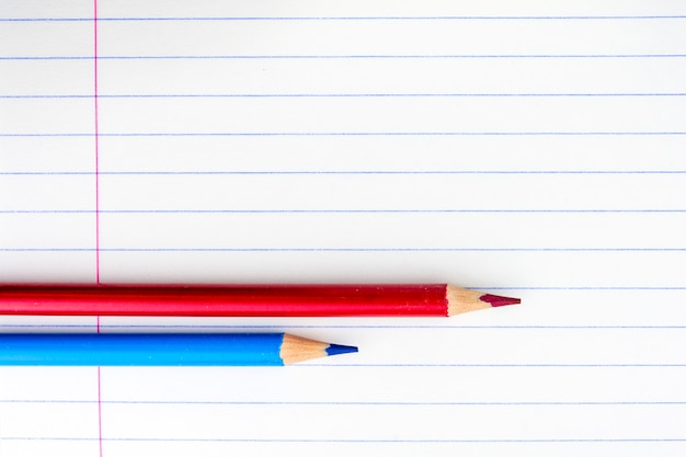 Sheet of a school notebook in the range. two pencils on the sheet. red and blue pencils.