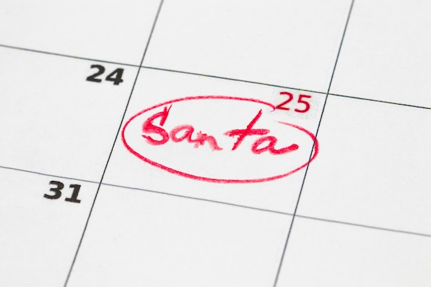 Sheet of wall calendar with red mark on 25 december - christmas, written santa.