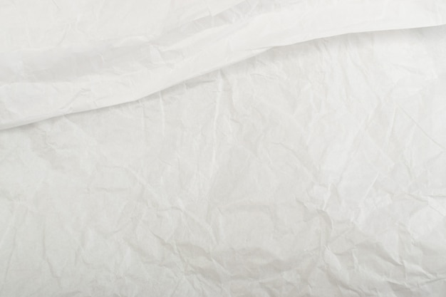 Sheet of white thin crumpled craft paper background top view.