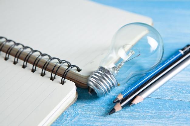 펜과 테이블 lk에 전구와 노트북 시트. 새로운 아이디어
