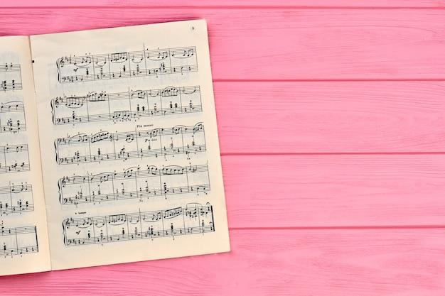 Лист с нотами, копией пространства. музыкальные ноты на розовом деревянном фоне.