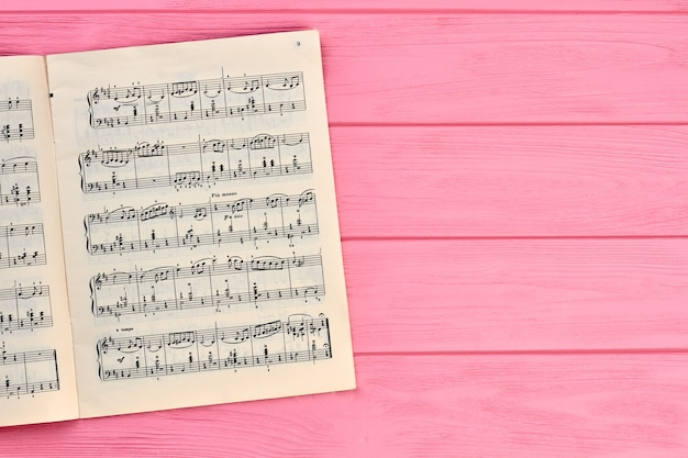Sheet with musical notes, copy space. musical notes on pink wooden background.