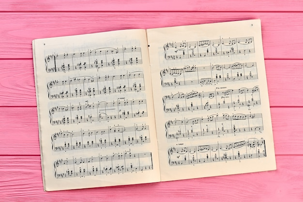 Sheet with musical notes, top view. musical notes on colorful wooden backgroud.