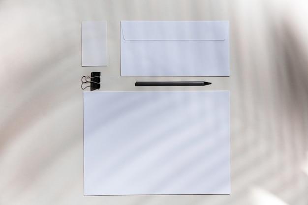 실내 흰색 테이블에 시트 및 작업 도구. 홈 오피스의 창의적이고 아늑한 직장, 표면에 식물 그림자로 영감을주는 모의. 원격 사무실, 프리랜서, 분위기의 개념.